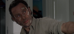 Rick holds out the gun for Michonne to take. Michonne makes no move to take the gun.