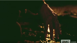 Deanna Monroe's bloodied hand, hanging limply, as the dying fire in the chiminea reflects in the pool Reg's blood.