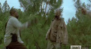 Morgan, squaring off with a walker, trusty wooden staff in hand. We see an outstretched hand cocking a pistol, ready to fire upon the walker, but Morgan's like,