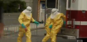 Liza sees the EMT's file out of the ambulance with head-to-toe hazmat suits to collect the body.