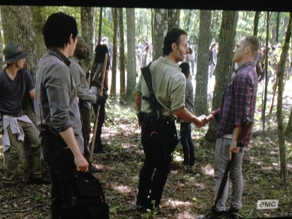Carter holds out a hand, and Rick takes it. The men shake, making peace.