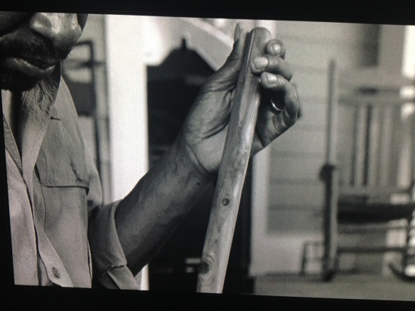 This scene shifts to the past, where Morgan sits outside on Rick's porch, polishing his staff.