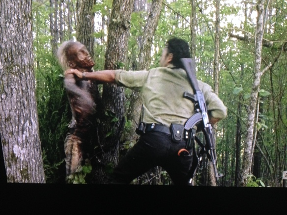 ...Rick quickly dispatches the tree walker with his knife.;