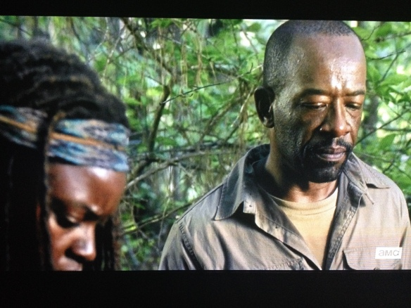 Michonne steps forward. They look down at the dead young man who lay at their feet.