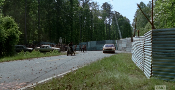 As the mass approaches, Rick, Morgan, and MIchonne begin firing well-timed, well-placed flares to distract the walkers' attention from charging full-forward into the wall, and lead them around the bend.
