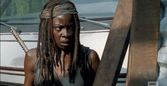 Michonne fires a flare, then edges closer, bracing herself, peering through the corner...
