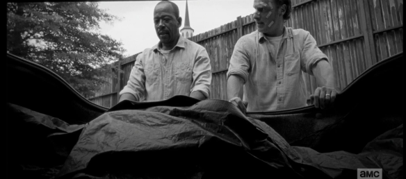 Later, as they load Pete's body into the car trunk, Rick looks over at Morgan.
