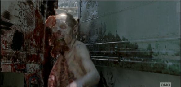 As the walker gets shoved through the narrow opening between the trucks, we see how its skin and soft tissues tear away easily from the bones. Greg Nicotero, you beautiful madman!