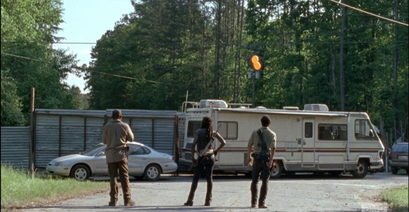 In the next scene, we see Rick, Michonne, and Morgan running ahead of the dreaded walker parade. Rick radios Glenn, checks in. It seems Glenn and the others are right on time, ahead of the horde, at the tractor store. As they regard the barricade they set up, before, RV and car parked in front of metal gates, Rick says,