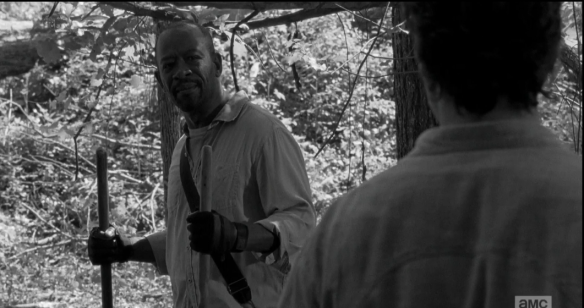Morgan smiles at Rick, taps the shovel in his right hand a few times into the ground, says,